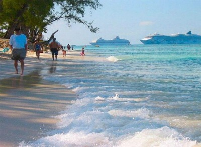 Cruise travelers enjoying the beach while cruise ships are anchored near George Town.